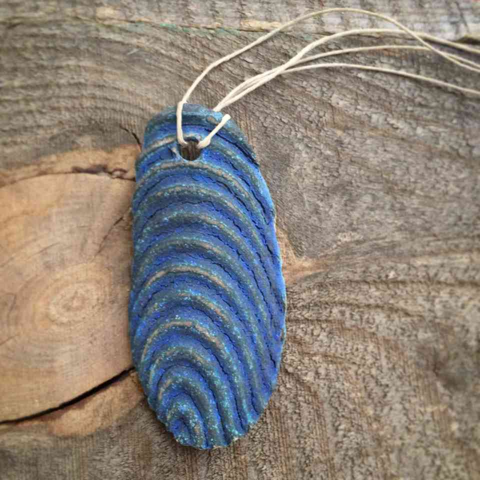 blue porcelain necklace shell shaped with a double hemp chord on a wood background