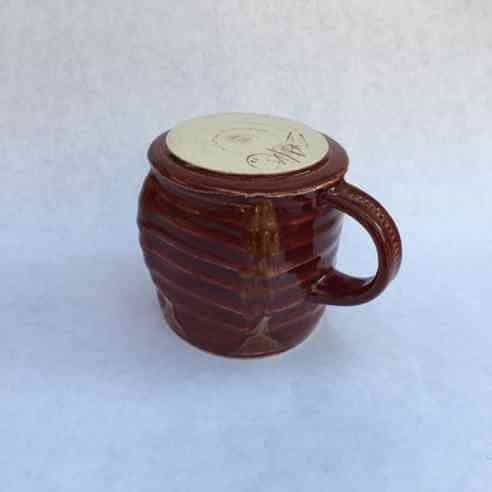 Bottom of Red Brown Glazed Mug with Handle on a blueish white background